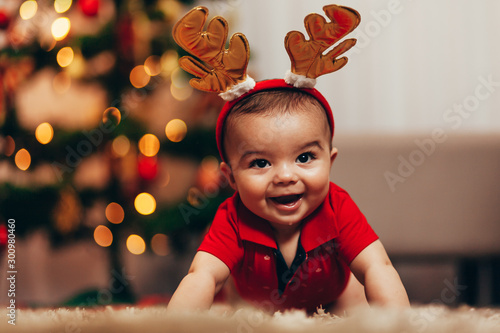 Cute baby boy wearing reindeer antlers crawling on floor over Christmas lights Fototapet