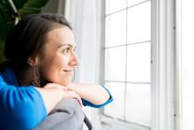 A Beautiful Woman Looking Through A Window