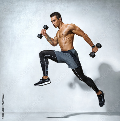 Sporty man jumping with dumbbells Canvas Print