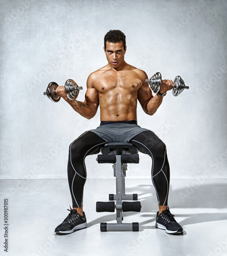 Photo  Man doing exercises with dumbbells on bench