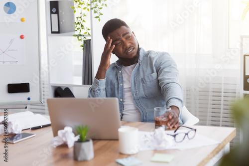 Stressed african american employee drinking alcohol in office Billede på lærred