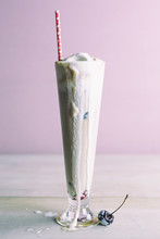 Tall Root Beer Float In A Pilsner Glass With Red Paper Straw, Melting Ice Cream And Cherry.