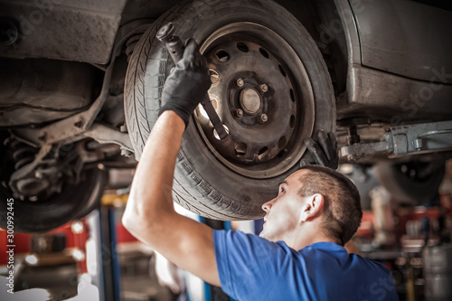 Auto master mechanic checks condition of the brakes and wheels Wallpaper Mural