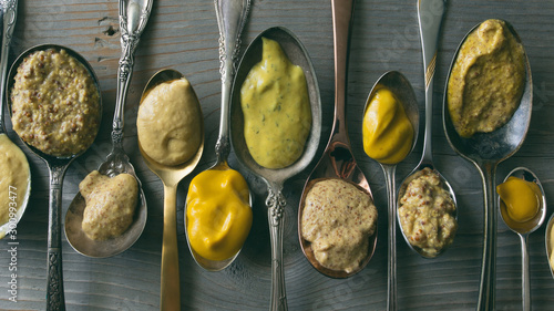 Valokuva Several types of mustard shown in spoons on a wooden background.
