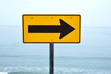 A Yellow Street Sign With Arrow Pointing Right At The Beach With A View Of The Ocean