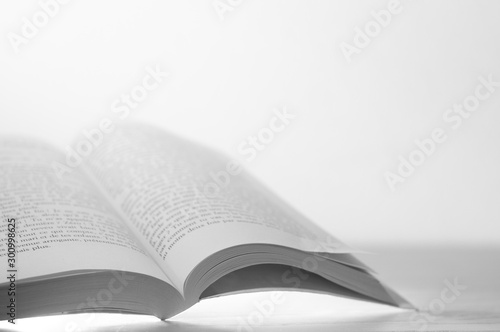 Fotomural Open book on wooden table and white background