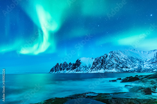Photo sur Toile Aurore polaire Vivid Northern lights during polar night on Lofoten Islands in Norway. Epic scene of dancing aurora borealis in the night sky over jagged mountain ridge and Arctic ocean on island Senja, polar circle.