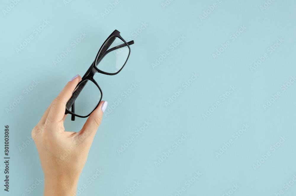 Fototapeta Hand with eyeglasses composition on blue background.