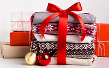 Many Bright Christmas Sweaters With Patterns Wrapped By Red Bow