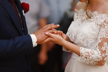 Two Gold Wedding Rings. The Bride Wears The Groom Wedding Ring. Newlyweds With  Rings On  Fingers.wedding Ceremony Outdoor. The Couple Exchanges The Wedding Rings. Just Married