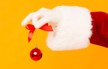 Santa Claus Holding Small Red Ball In Hand On Orange