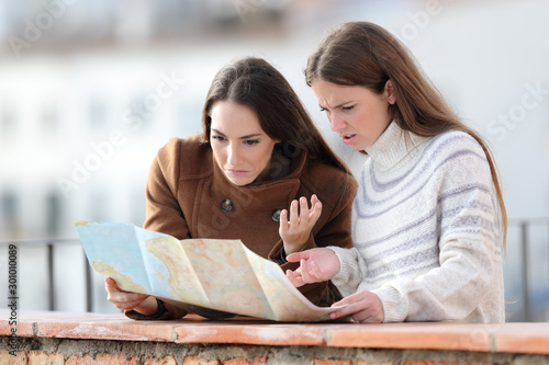 Lost tourists checking paper map in a balcony Canvas Print