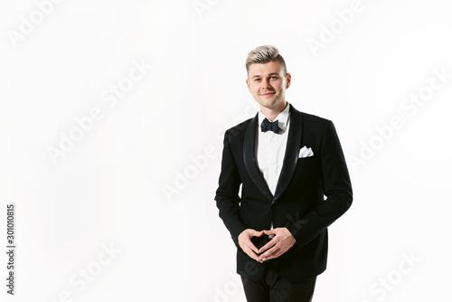 Valokuvatapetti Portrait of young smiling handsome man in tuxedo stylish black suit, studio shot isolated on white background