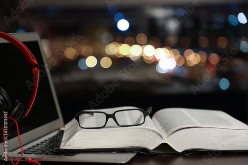 laptop with headphones and an open book with glasses, traditional reading and au Slika na platnu