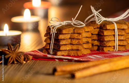 pila di biscotti legati con spago, cannella, chiodi di garofano e candele accese Fototapeta