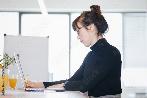 Fototapety, obrazy: Candid portrait of business woman working and taking notes during a meeting in modern office space. .