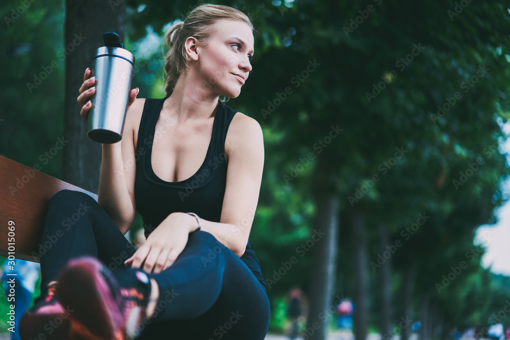 Fototapeta Charming good looking female runner resting on bench on urban setting after morning jogging around city, attractive sportswoman thoughtful looking away before starting hard workout on nature