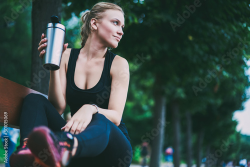 Obraz Charming good looking female runner resting on bench on urban setting after morning jogging around city, attractive sportswoman thoughtful looking away before starting hard workout on nature - fototapety do salonu