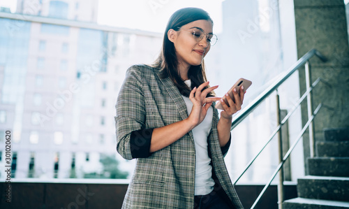 Fotomural  Smiling young woman sending message on smartphone standing on urban setting, pos