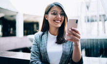 Happy Woman In Eyewear Smiling While Watching Trailer Of Future Comedy Connected To 4g Wireless For Browsing Movie Website, Cheerful Young Blogger Reading Received Message In Group Chat With Followers