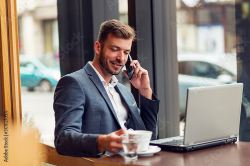 Fototapety, obrazy: Young businessman in suit sitting in cafe bar and talking on the phone