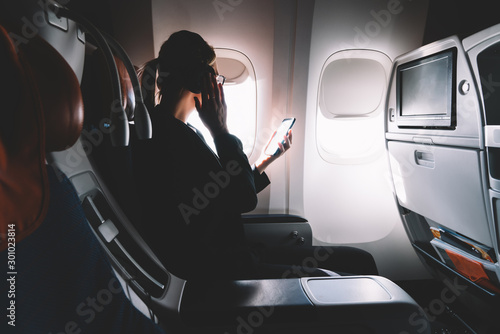 Obraz Successful female lawyer making intercontinental flight in first class listening music via electronic bluetooth headphones connected to airplane wifi for using smartphone application for melomans - fototapety do salonu
