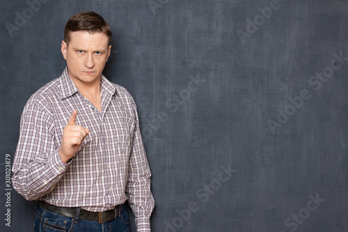 Fotomural  Portrait of serious concentrated man raising index finger