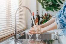 Woman Washing Hands In Sink Be...