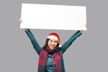Happy Woman In Christmas Theme Cloth With Santa Hat Presenting Blank Banner