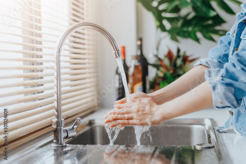 Fotografía  Woman washing hands in sink before cooking in kitchen