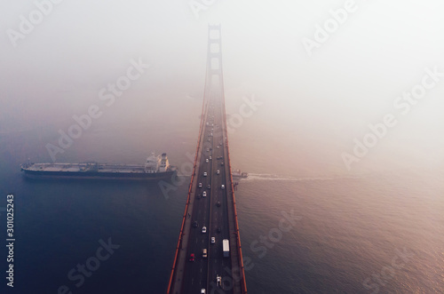 Foto auf Leinwand Lachs Aerial view of Golden Gate Bridge in foggy visibility during evening time, metropolitan transportation infrastructure, birds eye view of automotive car vehicles on road of suspension construction