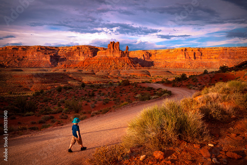 Photo sur Toile Rouge mauve Child walking alone in the desert canyon along a dirt road