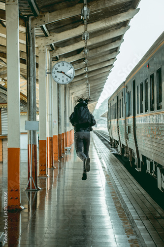 Fototapety, obrazy: The tourist man in black jumping in vintage train station, he is happy with his trip.