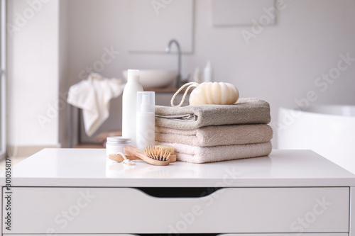 Photo  Stack of towels, cosmetics, loofah and brushes on table in bathroom