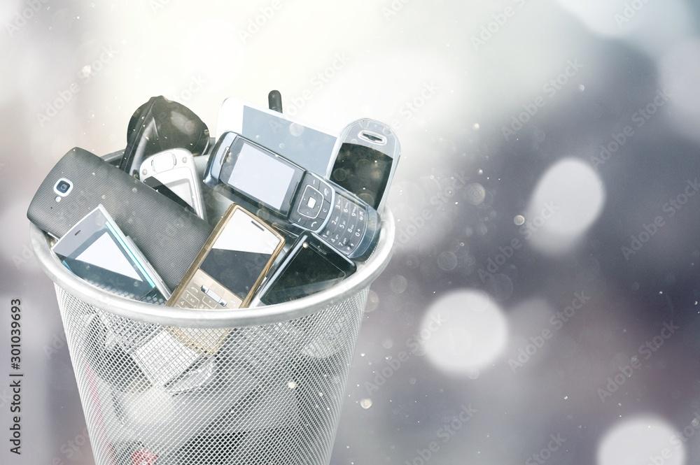 Fototapeta Rubbish bin full of old cellphones