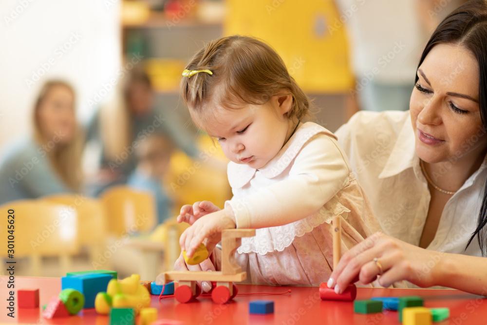 Fototapety, obrazy: Child building blocks with a teacher in the nursery