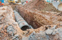 Concrete Drainage Tube Row Underground Near Construction Site.Concrete Pipe Stacked Sewage Water System Aligned On Site.