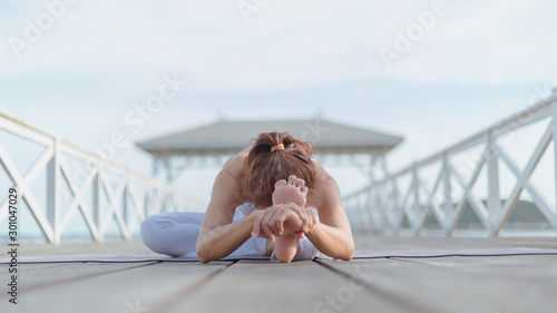 Young women practice yoga on the white bridge by the sea, the concept of enjoying privacy and the concentration of sunlight Canvas Print