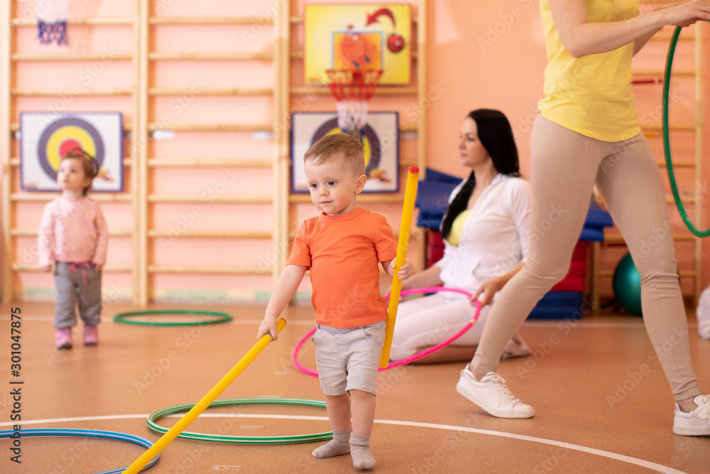 Fototapety, obrazy: Kids with moms in gym. Healthy lifestyle and baby sport concept