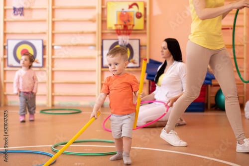 obraz lub plakat Kids with moms in gym. Healthy lifestyle and baby sport concept