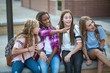 Leinwandbild Motiv Candid photo of a group of teenage girls socializing, laughing and talking together at school. A multi-ethnic group of real junior high aged students