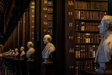 DUBLIN, IRELAND, DECEMBER 21, 2018: The Long Room In The Trinity College Library, Home To The Book Of Kells. Perspective View Of The Place, With Large Quantity Of Books And Chest Statues.