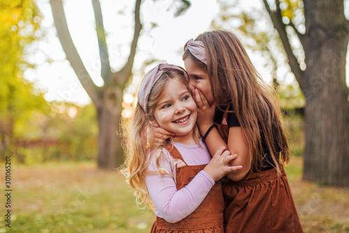 Fototapeta Portrait of two little sisters in a park, whispering secrets. obraz
