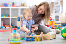 Cheerful Baby Playing With Toys With Happy Mother In Nursery Room