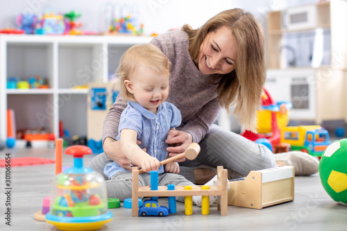 Cheerful baby playing with toys with happy mother in nursery room Canvas Print