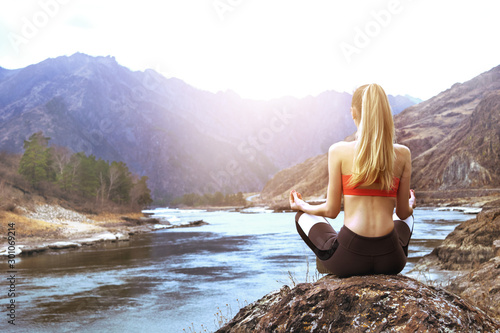 woman sits yoga pose rock against backdrop mountains river