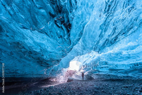 Tourist standing in an ice cave in Vatnajökull glacier Iceland