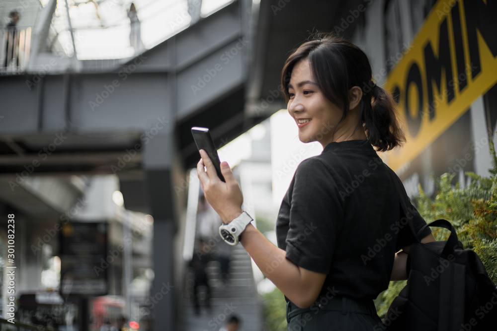 Fototapety, obrazy: Happy asian woman looking at her phone in the city