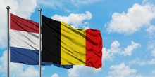 Netherlands And Belgium Flag Waving In The Wind Against White Cloudy Blue Sky Together. Diplomacy Concept, International Relations.