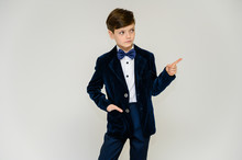 Concept Boy Teenager Shows Imitates Entertainer Behavior On Stage. Portrait Of A Child On A White Background In A Dark Blue Concert Suit. Standing In Front Of The Camera In Poses With Emotions.
